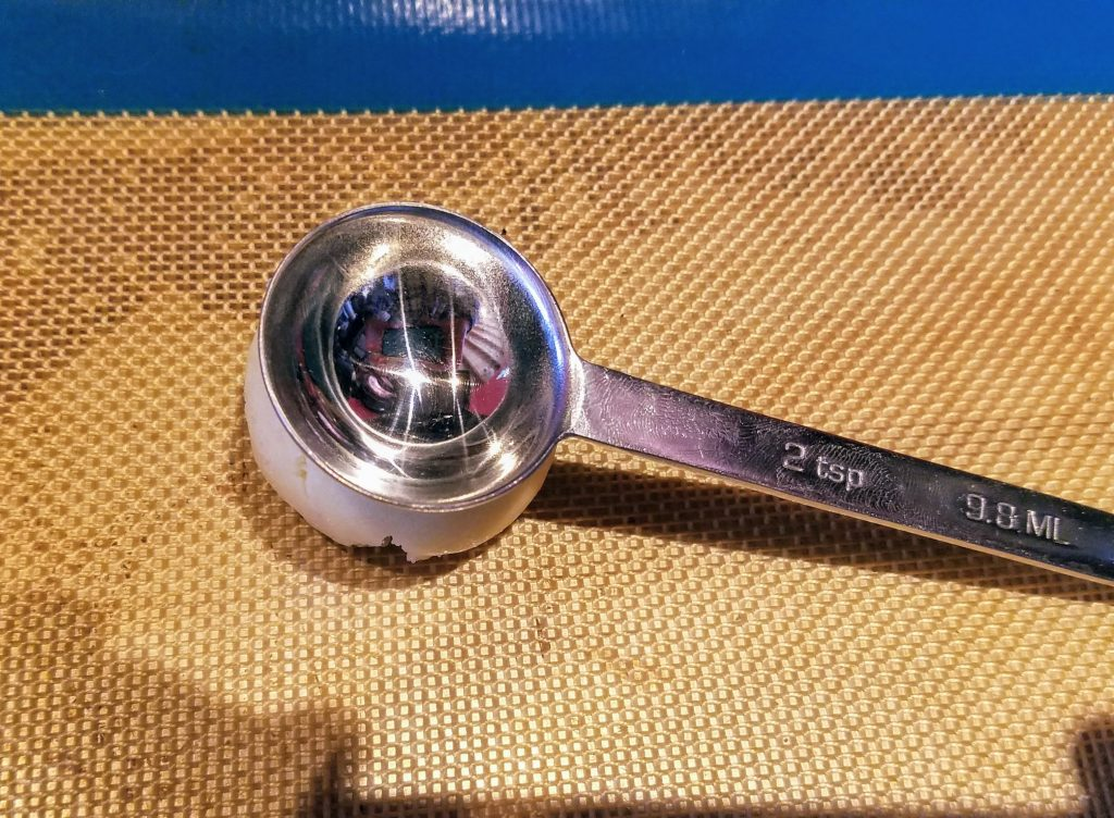 use a metal measuring spoon to make the well