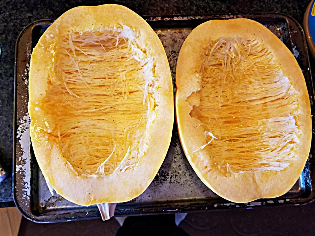 spaghetti squash cut in half on baking sheet