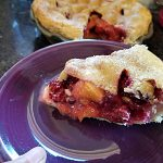 slice of peach blackberry pie on a purple plate